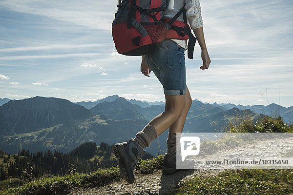 Austria  Tyrol  Tannheimer Tal  young woman hiking on mountain trail