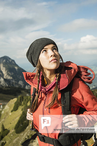 Austria  Tyrol  Tannheimer Tal  young woman looking up