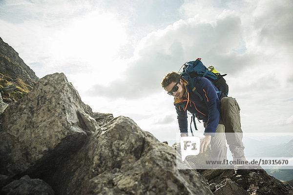 Österreich  Tirol  Tannheimer Tal  junger Mann beim Klettern am Fels
