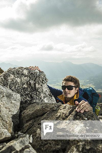 Austria  Tyrol  Tannheimer Tal  young man climbing on rock