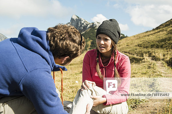 Austria,  Tyrol,  Tannheimer Tal,  young man caring for injured woman on hiking tour