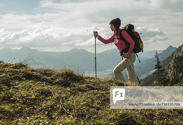 Austria  Tyrol  Tannheimer Tal  young woman hiking on alpine meadow
