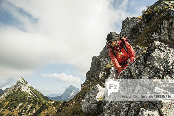 Austria  Tyrol  Tannheimer Tal  young woman hiking on rock