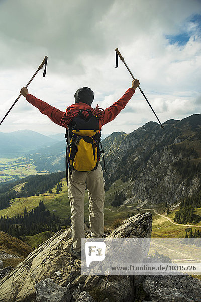 Austria  Tyrol  Tannheimer Tal  young woman with hiking poles cheering on mountain top