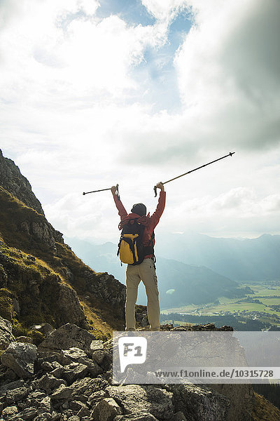 Austria,  Tyrol,  Tannheimer Tal,  young woman with hiking poles cheering on mountain top