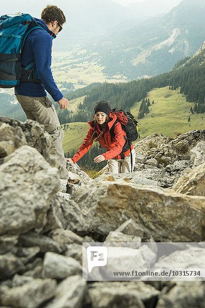 Austria  Tyrol  Tannheimer Tal  young couple hiking on rocks