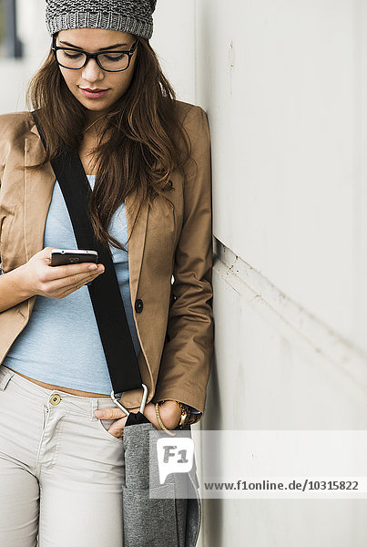 Junge Frau lehnt sich an eine Wand und liest SMS.