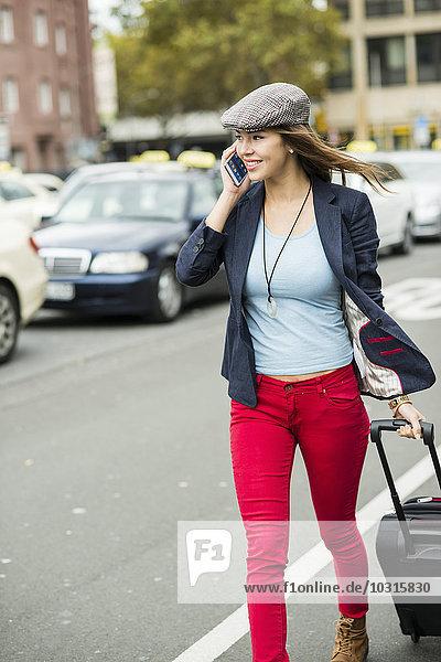 Junge lächelnde Frau mit Smartphone und Rollgepäck  die eine Straße entlang läuft