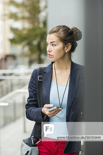 Junge ernsthaft aussehende Frau mit Smartphone wartend