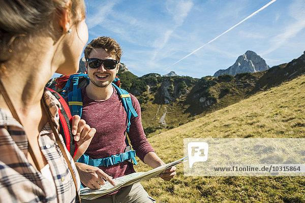 Österreich  Tirol  Tannheimer Tal  junges Paar Wandern mit Karte