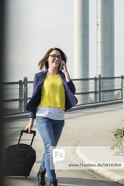 Lächelnde junge Frau mit Gepäck am Handy