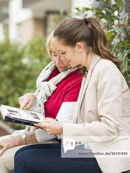 Enkelin und Großmutter beim Betrachten des Fotoalbums