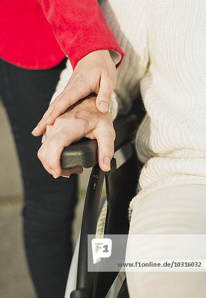 Hand der jungen Frau auf Hand der älteren Frau im Rollstuhl sitzend