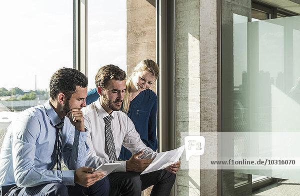 Drei junge Geschäftsleute beim Betrachten von Dokumenten und digitalen Tabletts