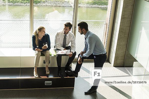 Drei junge Geschäftsleute diskutieren über das Dokument