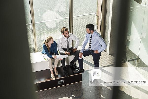 Drei lächelnde junge Geschäftsleute diskutieren Dokument