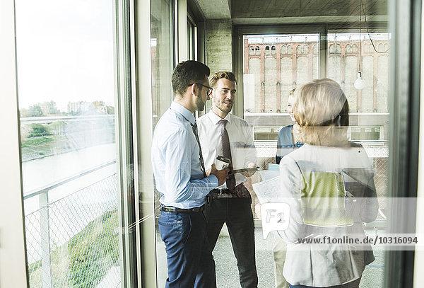 Geschäftsleute mit Dokumenten  die am Fenster reden.