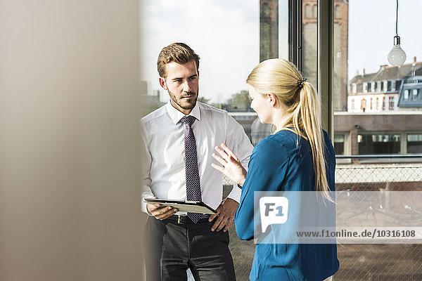 Junge Geschäftsfrau und Geschäftsmann mit digitalem Tablett im Gespräch