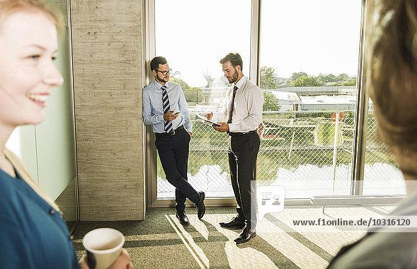 Zwei junge Geschäftsleute im Gespräch am Fenster im Büro mit Kollegen im Vordergrund
