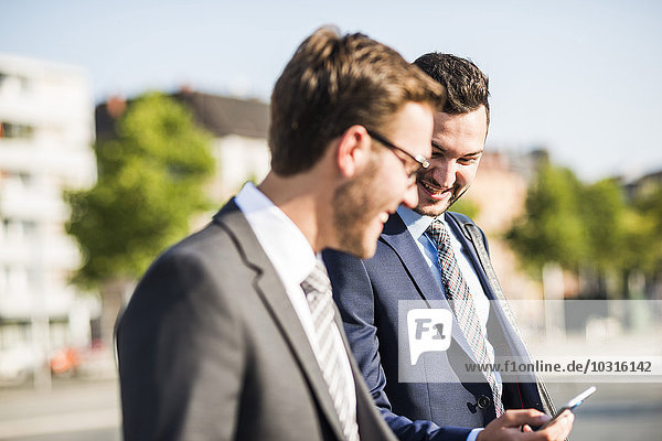 Two young businessmen walking in city  looking at mobile phone