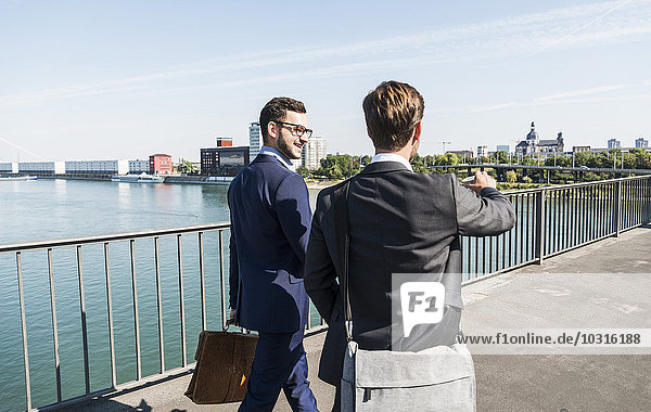 Two young business colleagues walking by river  discussing