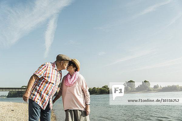 Deutschland  Ludwigshafen  küssendes Seniorenpaar am Flussufer