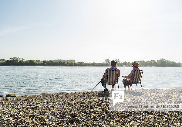 Germany  Ludwigshafen  back view of senior couple sitting side by side on folding chairs at riverside