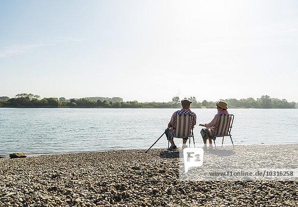 Deutschland  Ludwigshafen  Rückansicht des Seniorenpaares auf Klappstühlen am Ufer des Flusses