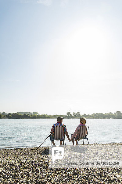 Germany  Ludwigshafen  back view of senior couple sitting hand in hand on folding chairs at riverside