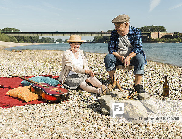 Germany,  Ludwigshafen,  senior couple barbecueing sausages on the beach