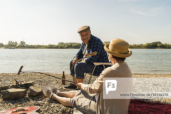 Germany  Ludwigshafen  senior couple barbecueing sausages on the beach