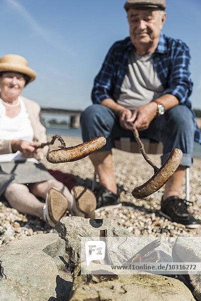 Deutschland  Ludwigshafen  Seniorenpaar Grillwürste am Strand