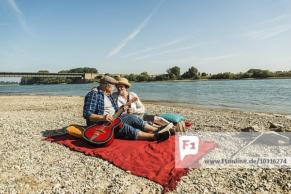 Germany  Ludwigshafen  senior couple relaxing with guitar on blanket on the beach
