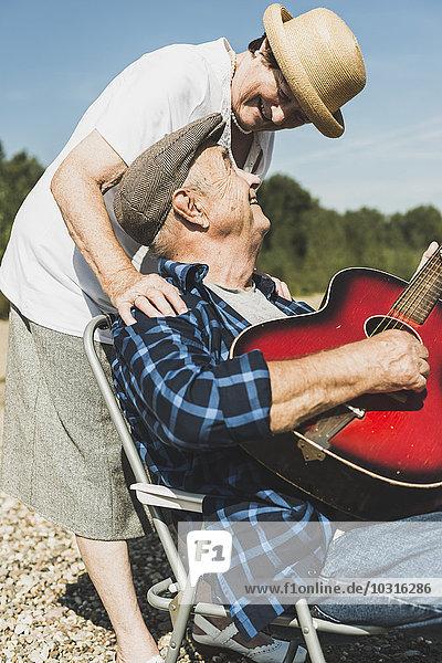 Glückliches Seniorenpaar mit Gitarre