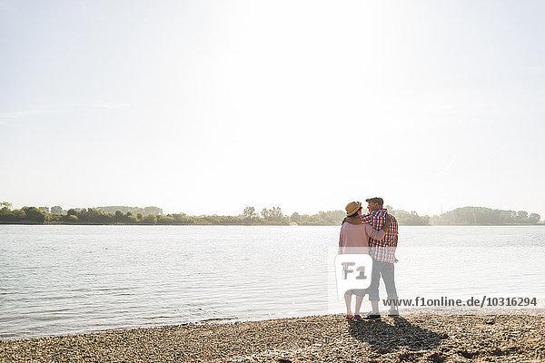 Deutschland  Ludwigshafen  Seniorenpaar mit Arm in Arm am Flussufer