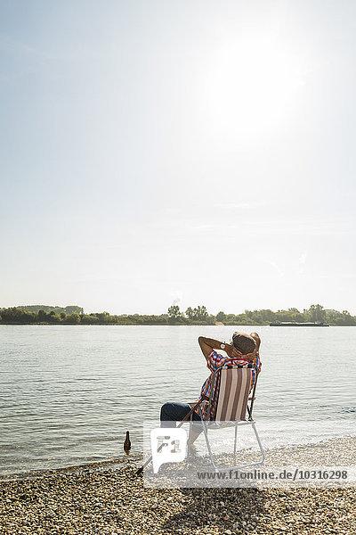 Deutschland  Ludwigshafen  Rückansicht des Seniorchefs rrlaxing auf Klappstuhl am Flussufer