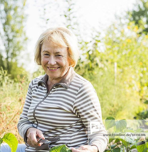 Porträt der lächelnden Seniorin im Garten