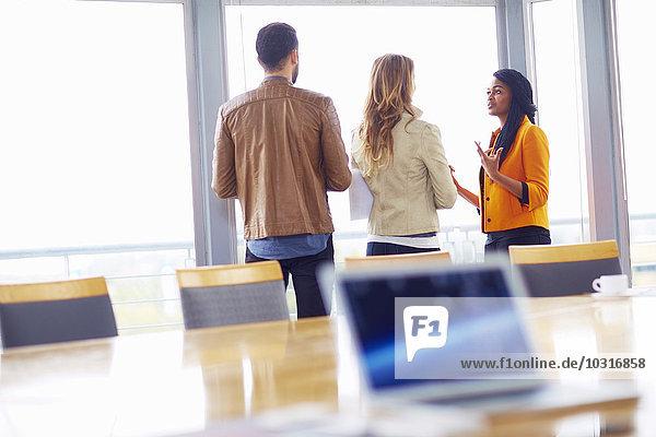 Drei kreative Menschen stehen in einem Konferenzraum