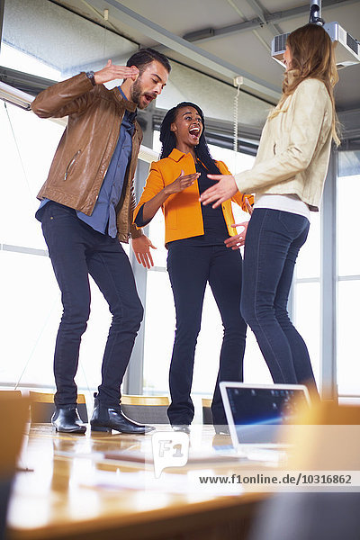 Drei fröhliche Kreative tanzen auf einem Konferenztisch