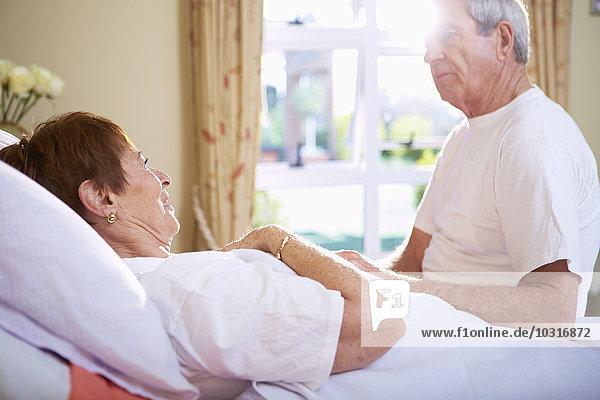 Seniorenfrau im Krankenhausbett im Gespräch mit Seniorenmann