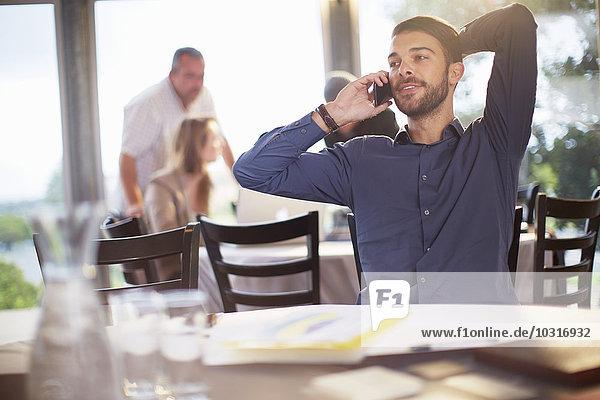 Portrait eines Geschäftsmannes beim Telefonieren mit dem Smartphone im Restaurant