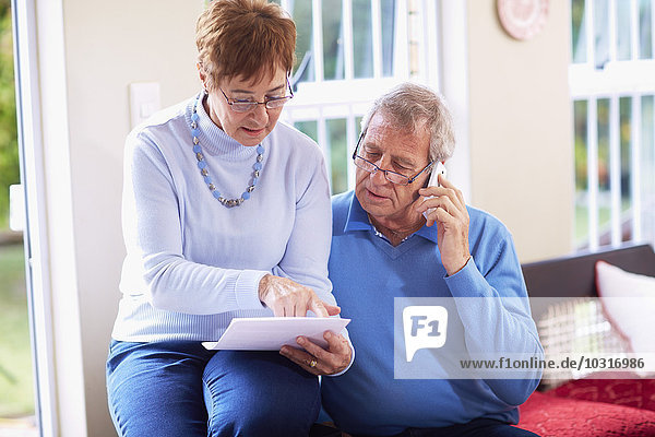 Seniorenpaar liest Dokument zu Hause