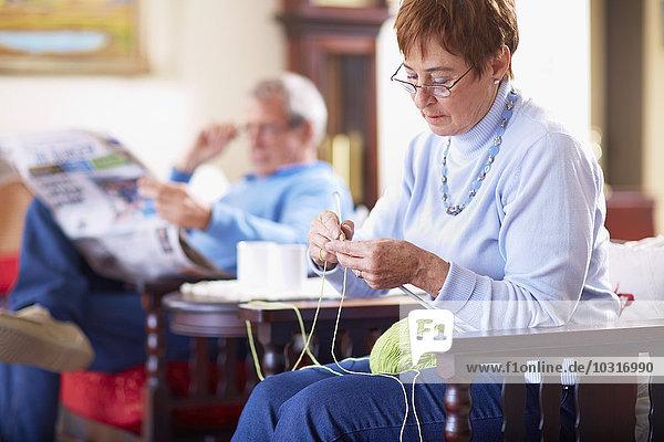 Seniorin strickt mit Mann im Hintergrund Zeitung lesen