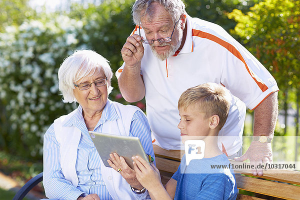 Grandson and grandparents using digital tablet in park