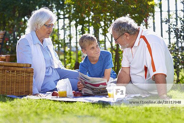 Großeltern mit Enkel beim Picknick im Park