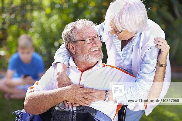 Seniorin umarmt Ehemann im Rollstuhl