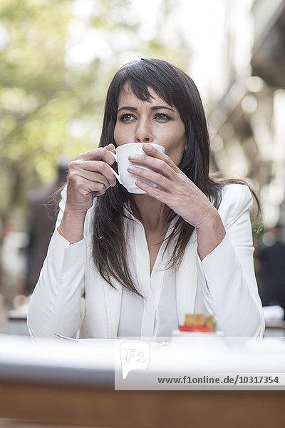 Frau trinkt Kaffee im Außencafé Frau trinkt Kaffee im Außencafé