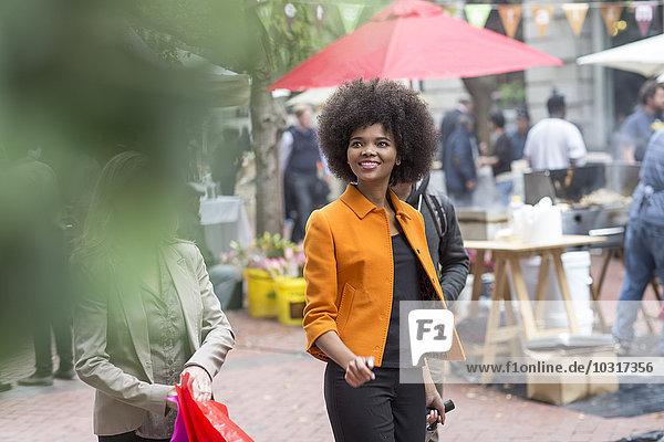 Lächelnde Frau geht mit Koffer durch die Stadt