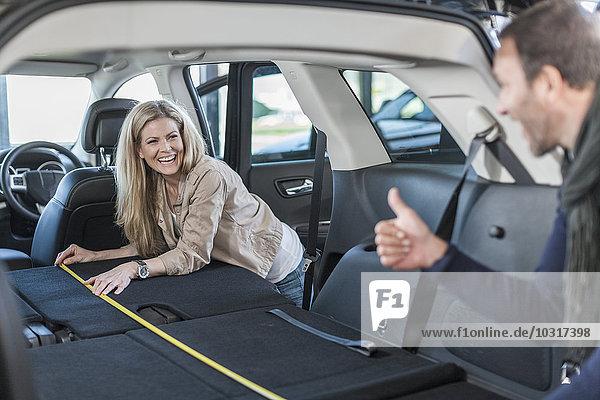 Paar untersucht neues Auto bei einem Autohändler