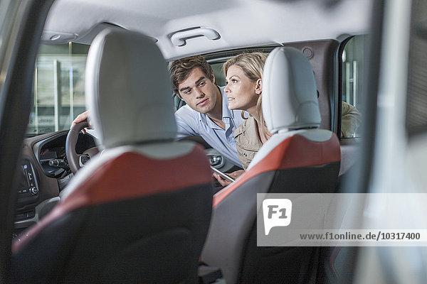 Autohändler zeigt neues Auto der Frau